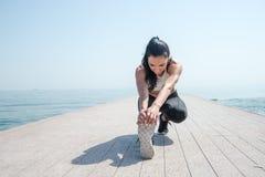 Young beautiful sportive girl preparing to run. Over seaside Stock Photography