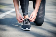 Young beautiful sportive girl preparing to run. In the park Royalty Free Stock Photos