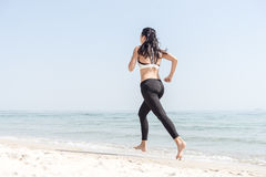 Young beautiful sportive girl runing. Over seaside Royalty Free Stock Photos