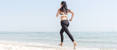 Young beautiful sportive girl runing. Over seaside Royalty Free Stock Photo