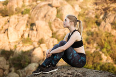 Young beautiful sportive girl smiling, sitting on rock in canyon. Royalty Free Stock Image