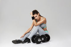 Young beautiful sportive girl in sportswear looking at camera sitting with dumbbells over white background. Copy space Stock Images