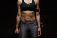 Young beautiful sportive girl training over dark background. Close up. Royalty Free Stock Photos