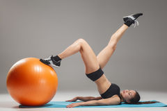 The young, beautiful, sports girl doing exercises on a fitball. At the gym on gray background Stock Photos