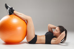 The young, beautiful, sports girl doing exercises on a fitball. At the gym on gray background Royalty Free Stock Photo