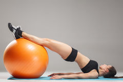 The young, beautiful, sports girl doing exercises on a fitball. At the gym on gray background Stock Image