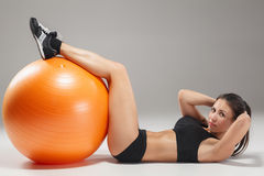 The young, beautiful, sports girl doing exercises on a fitball. At the gym on gray background Royalty Free Stock Image