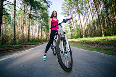 Young beautiful sports girl on a white bicycle in the woods Stock Images