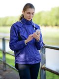 Young Beautiful Sports Woman Using her Phone in the Park Stock Photos