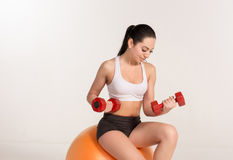 Young beautiful sportswoman with dumbbells exercising on fitball Stock Photos