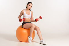 Young beautiful sportswoman with dumbbells exercising on fitball Royalty Free Stock Photo