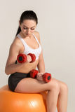 Young beautiful sportswoman with dumbbells exercising on fitball Stock Image