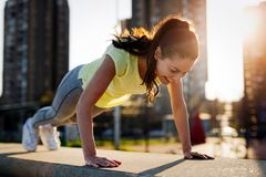 Young sportswoman stretching and preparing to run. Royalty Free Stock Photos