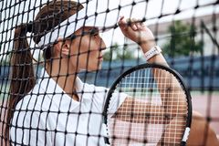 Young beautiful sportswoman with tennis racket sitting at tennis net on tennis court. Sports Fashion Royalty Free Stock Photo
