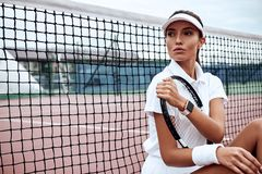 Young beautiful sportswoman with tennis racket sitting at tennis net on tennis court. Sports Fashion Royalty Free Stock Images