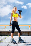 Young, beautiful, sporty and fit girl rollerblading on inline sk Royalty Free Stock Photography