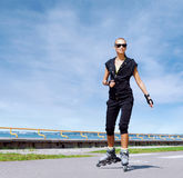 Young, beautiful, sporty and fit girl rollerblading on inline sk Royalty Free Stock Image
