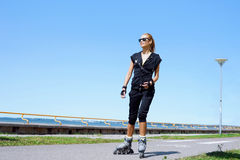 Young, beautiful, sporty and fit girl rollerblading on inline skates Stock Image