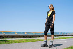 Young, beautiful, sporty and fit girl rollerblading on inline skates Royalty Free Stock Photography