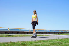 Young, beautiful, sporty and fit girl rollerblading on inline skates Royalty Free Stock Image