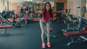 Athletic young woman doing exercises with dumbbells in the gym. 4 k. Young beautiful sporty girl brunette with long hair doing exercises with dumbbells in the stock video