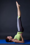 Young beautiful sporty girl doing legs up exercise over grey Stock Photo