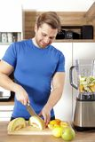 Young beautiful man is making a smoothy with a mixer stock photography