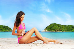 Young, beautiful, sporty and sexy woman using the suntan cream Royalty Free Stock Image