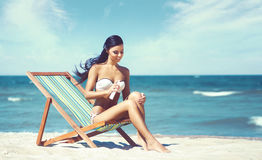 Young, beautiful, sporty and sexy woman using the suntan cream o Royalty Free Stock Photo