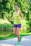 Young beautiful sporty slim woman running in park. Young beautiful sporty slim woman running in summer park Stock Photography