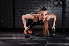 Young beautiful sporty woman in the black sportwear doing a pushups with kettlebell at the crossfit gym. Royalty Free Stock Image