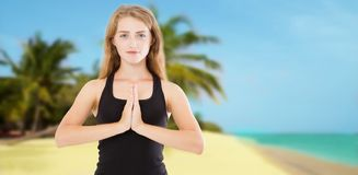 Young beautiful sporty woman doing yoga exercise on sea wooden beach near water. Girl practicing exercises mudra. Hands in namaste. Gratitude sign. Health royalty free stock images