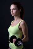Young beautiful sporty woman with dumbbell over grey Stock Image