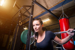 Young beautiful sporty woman exercising with barbell in gym royalty free stock images