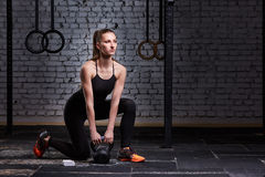 Young beautiful sporty woman holding kettlebell on the gym floor against brick wall. Woman in the black sportwear, t-shirt, leggings and sportive shoes Royalty Free Stock Photos