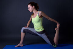 Young beautiful sporty woman stretching legs over grey Stock Photo