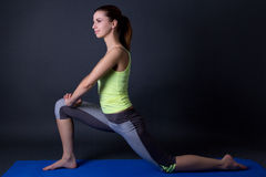 Young beautiful sporty woman stretching legs on yoga mat over gr Royalty Free Stock Photos