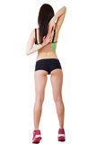 Young beautiful sporty woman wearing sports shorts and top stands with his back Stock Photos