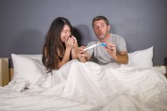 Young beautiful and stressed couple in bed looking pregnancy test feeling happy and surprised by positive pregnant result looking stock images