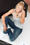 Young beautiful student chats over the mobile. While sitting on floor stock image