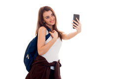 Young beautiful student girl with backpack makes selfie isolated on white background in studio Royalty Free Stock Photo
