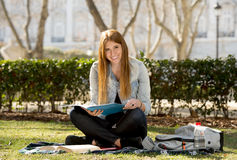 Young beautiful student girl on campus park grass with books studying happy preparing exam in education concept Stock Photo