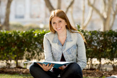 Young beautiful student girl on campus park grass with books studying happy preparing exam in education concept Stock Photos