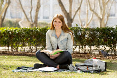 Young beautiful student girl on campus park grass with books studying happy preparing exam in education concept Royalty Free Stock Photography