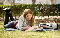 Young beautiful student girl on campus park grass with books studying happy preparing exam in education concept. Young beautiful student girl lying on campus Stock Image