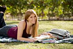 Young beautiful student girl on campus park grass with books studying happy preparing exam in education concept. Young beautiful student girl lying on campus Royalty Free Stock Photography