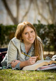 Young beautiful student girl on campus park grass with books studying happy preparing exam in education concept Stock Images