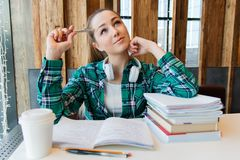 Young beautiful student girl is doing her homework or preparing to the exams siting with books copybooks. And cup of coffee. smiling royalty free stock images