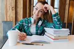 Young beautiful student girl is doing her homework or preparing to the exams siting with books copybooks. And cup of coffee. smiling stock image