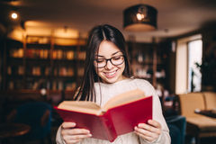 Young beautiful student girl reading a book Stock Photography